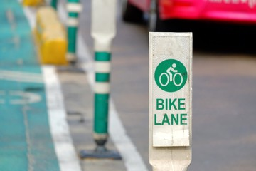 A bicycle lane sign on the white board at urban street area with blurred a car driving on the road