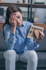 sad woman in blue blouse sitting on grey couch, looking at photo frame and crying at home, grieving disorder concept