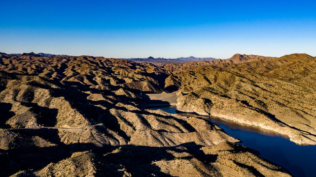 Aerial, drone view of Alamo Lake, Arizona in the remote desert near Wenden with vivid blue water and sky with Alamo Dam