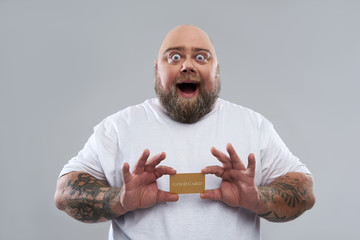 Funny bearded man feeling excited while holding gold card