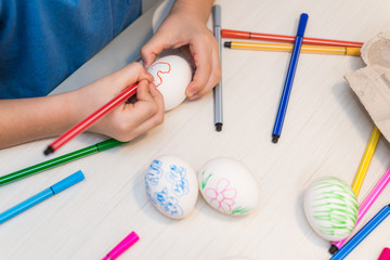 A child will paint Easter eggs with felt-tip pens. Easter ideas. Space for text. Egg tray. Happy easter.