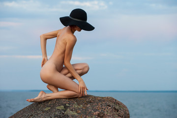 nude woman posing on the beach