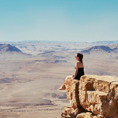 Girl sitting on a cliff and looking at desert