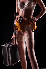 The girl builder is holding working tools on the background leather belt