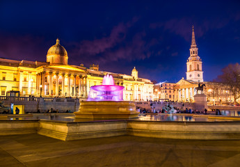 Fotobehang Madrid Cityscape view of the famous Trafalgar square of London in evening lights, with colorful fountains and artistic architecture of National Gallery in England