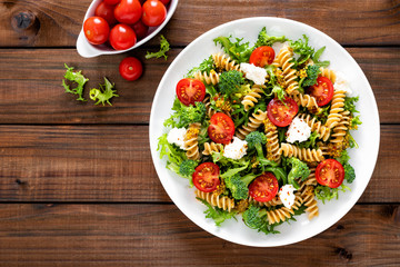 Italian pasta salad with wholegrain fusilli, fresh tomato, cheese, lettuce and broccoli on wooden rustic background. Mediterranean cuisine. Cooking lunch. Healthy diet food. Top view Fototapete