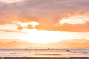 The clouds shapes absorb the color of the soft sun as it sets in Gisborne, New Zealand.