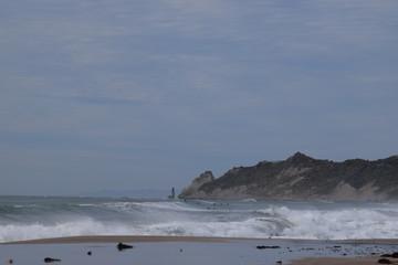 Large waves crashing on the empty beach in Gisborne, New Zealand.