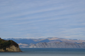 The shoreline meets the hill over the beach in Gisborne, New Zealand.