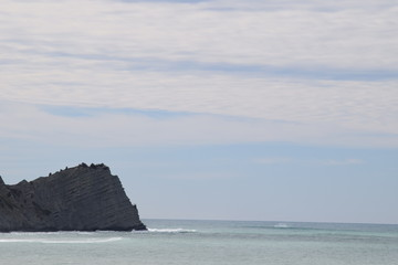 The sea hits the rocks at the shoreline in Gisborne, New Zealand.