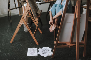 Barefooted woman sitting on the chair and her drawings lying on the floor