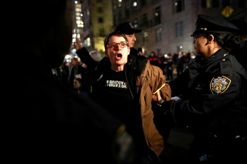 A person is detained during a protest against U.S. President Donald Trump's declaration of a national emergency to build a border wall, outside Trump International Hotel & Tower in Manhattan