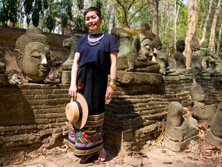 Femme en habit traditionnel Thaïlandais au milieeu des boudhas scuptés anciens du Wat Umong