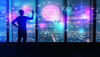 English with man writing on large windows high above a sprawling city at night