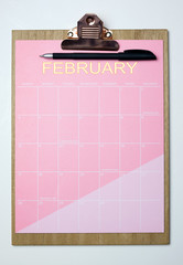 Top view of clipboard and pink sheet written with February