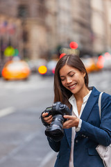 Asian woman photographer taking pictures with professional dslr camera on photography course in New York city street, NYC Usa travel.