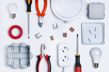 Different electrical tools on light grey background, top view. Electricity concept.