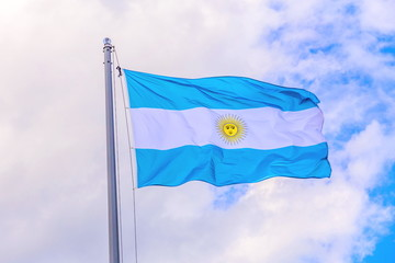 The national flag of Argentina flutters in the wind against the blue cloudy sky.