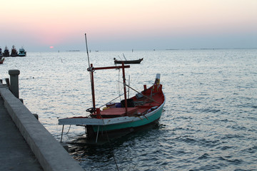 small fishing boat in the sea and sunset sky