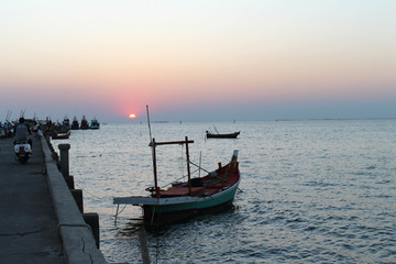 small fishing boat in the sea and harbor and sunset sky background