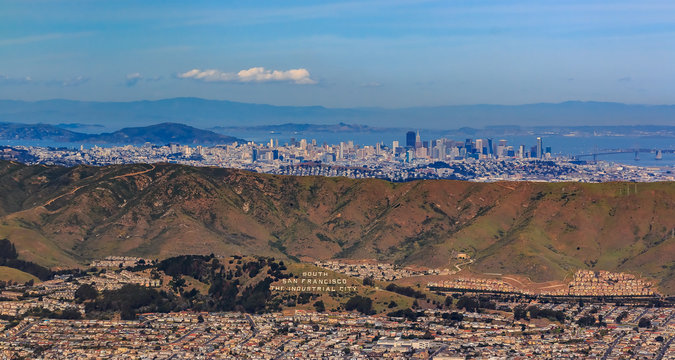 Aerial view of downtown San Francisco and Financial District sky scrapers flying over South San Francisco The Industrial City inscription on San Bruno mountain circa 2015