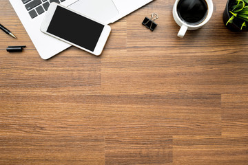 Wood office desk table with laptop, smartphone, cup of coffee and office supplies. Top view with copy space, flat lay.