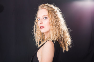 Fashion and model concept - Portrait of beautiful young sexy blond woman in a black dress posing against a white wall with copy space
