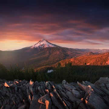Dramatic and Majestic View of Mt. Hood on a bright, colorful sunset during the summer months. The Pacific Northwest, Oregon, USA Mount Hood reflecting in Lake in Mount Hood National Forest