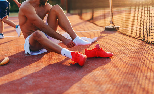 Sporty shirtless man putting on sock while sitting on the playground in the morning at summertime.