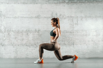 Side view of smiling sporty Caucasian woman dressed in sportswear and with ponytail doing lunges in the gym. In background wall. Wall mural