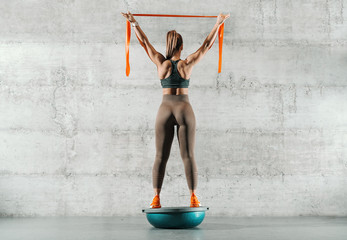 Woman holding ribbon and standing on bosu ball. Backs turned, wall in background. Wall mural