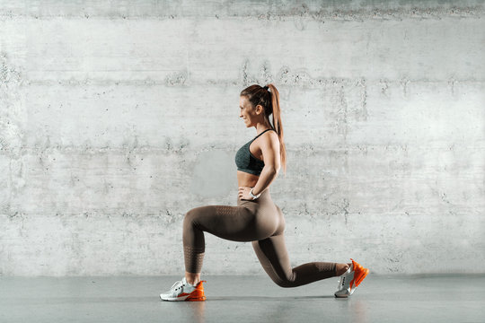 Side view of smiling sporty Caucasian woman dressed in sportswear and with ponytail doing lunges in the gym. In background wall.