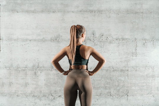 Caucasian sporty woman dressed in sportswear and with ponytail holding hands on hips and standing in the gym. In background wall, backs turned.