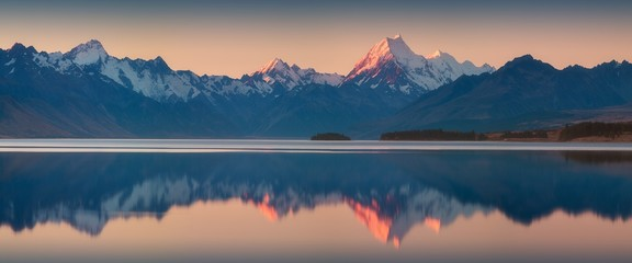 Snowy mountain range reflected in the still water of Lake Pukaki, Mount Cook, South Island, New Zealand. The turquoise water comes from Mt. Cook and Tasman glacier. Popular travel destination