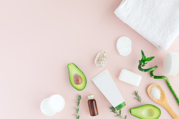 Layout of green white pink spa and wellness frame with towel, bamboo, tropical leaves , avocado, bottle of oil, body and face care tools on pastel background. Flat lay, top view.