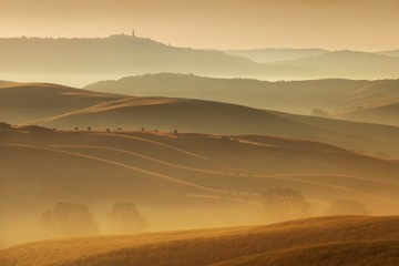 Tuscany landscape at sunrise. Typical for the region tuscan farmhouse, hills, vineyard. Italy Fresh Green tuscany landscape in spring time. Beautiful foggy landscape concept