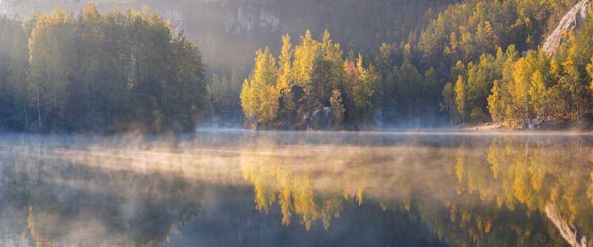 Autumn forest reflected in water. Colorful autumn morning in the mountains. Colourful autumn morning in mountain lake. Foggy autumn sunrise. Beautiful autumn background concept.