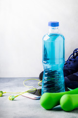Female fitness concept: light green dumbbells, isotonic blue water, smartphone with headphones and running shoes on gray concrete floor, selective focus