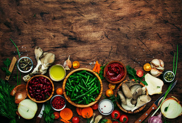 Food cooking background, ingredients for preparation vegan dishes, vegetables, roots, spices, mushrooms and herbs. Healthy food concept. Rustic wooden table background, top view. Copy space