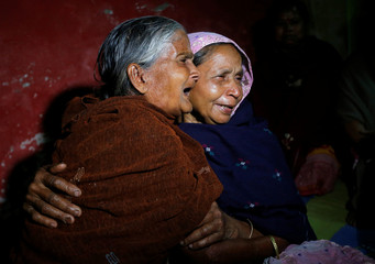 Elderly woman cries as she hugs Bonomala Santra, mother of Bablu Santra, a CRPF personnel who was killed after a suicide bomber rammed a car into the bus carrying CRPF personnel in south Kashmir on Thursday, at Bauria village in Howrah district