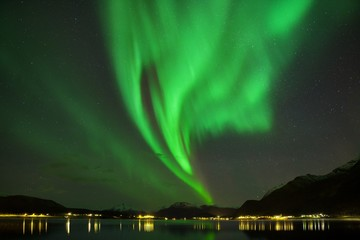 Universal photo with Aurora borealis dancing on a mountains. Beautiful northern lights above the mountains and the harbor and the coast Beautiful northern lights background concept. Night photo Tromso
