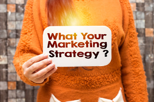 business woman holding white carton  paper with what your marketing strategy ? text
