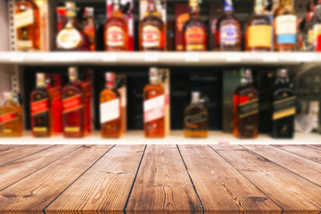 Wood table top and wine Liquor bottle on shelf blurred background Fototapete