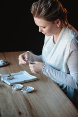 Portrait of young woman, creating wedding jewelry, workplace of decorator. Woman's hands in a process of creation
