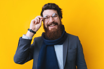 Handsome bearded businessman with scarf, touching his round glasses and looking at camera