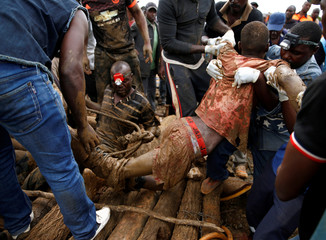 A rescued artisanal miner is carried from a pit in Kadoma