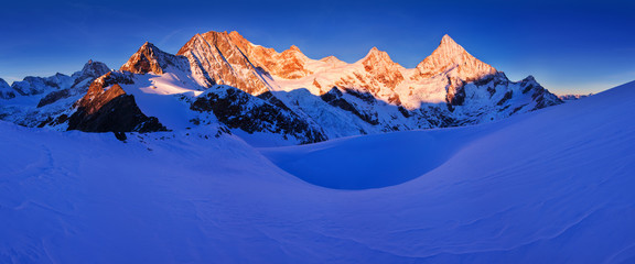 Photo sur Plexiglas Bleu fonce View of snow covered landscape with Dent Blanche mountains and Weisshorn mountain in the Swiss Alps near Zermatt. Panorama of the mountains in Switzerland. Beautiful morning with first snow. Christmas