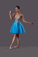 Ballerina wearing blue dress posing in studio