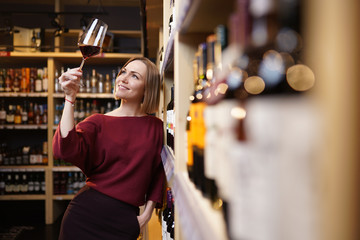 Picture of young girl with wine glass in store on background of shelves