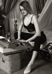 young beautiful woman typing on a retro typewriter. female writer in bra and men's trousers. black and white